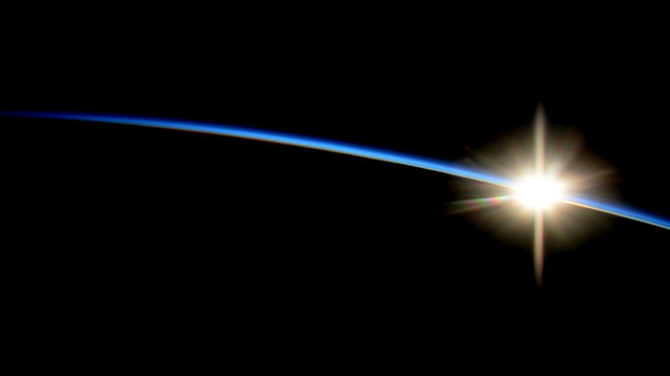 地球を包む酸素の大気が日を受けて青く輝く様子。