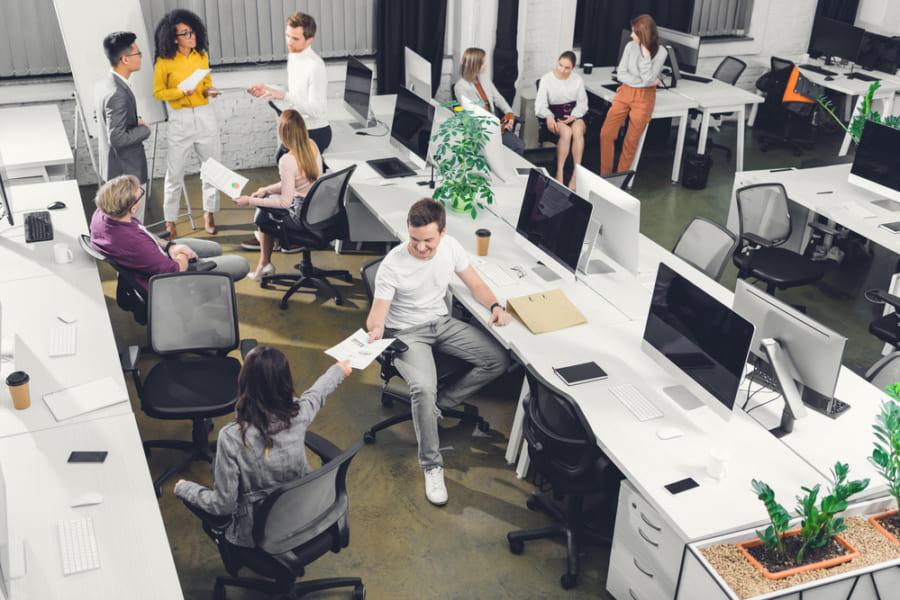 パソコンの乗った机の並ぶオフィス。