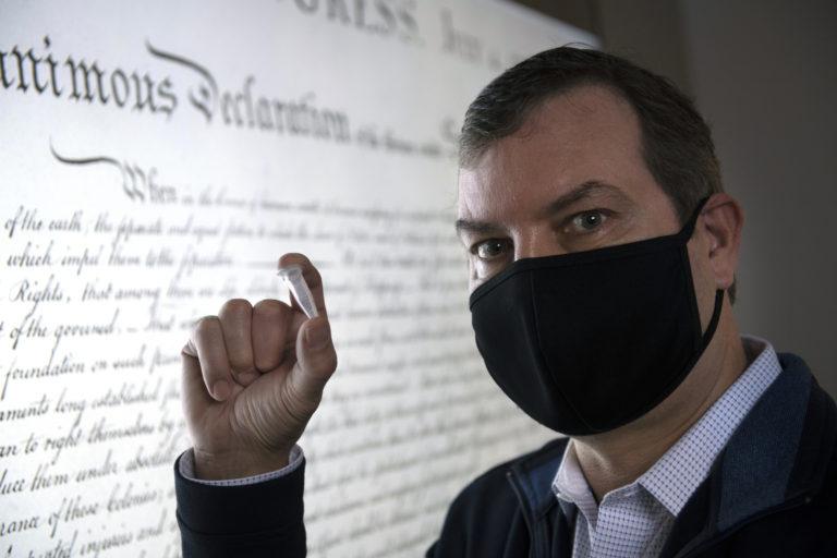 独立宣言文とUCIのマークを保存したTNAを手にしたジョン・シャプー氏。