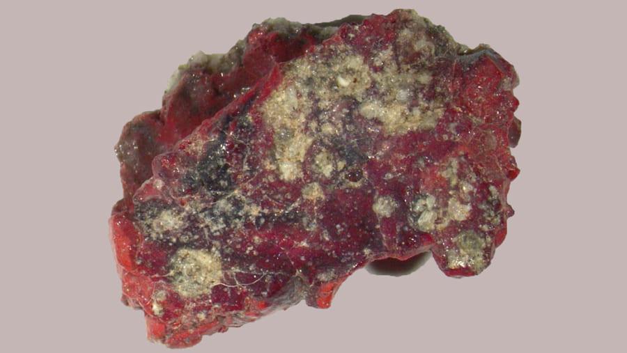赤いトリニタイト。これは核爆発で溶けた砂、銅線、その他の破片の融合で形成されている。