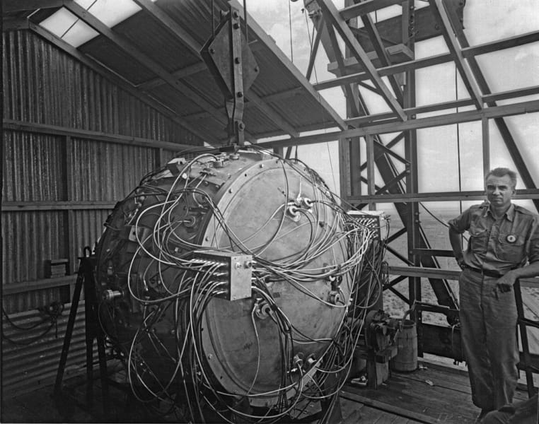 実験用の鉄塔の上に設置された核爆弾。隣に立っているのは爆弾組み立て班のリーダーノリス・ブラッドベリー。