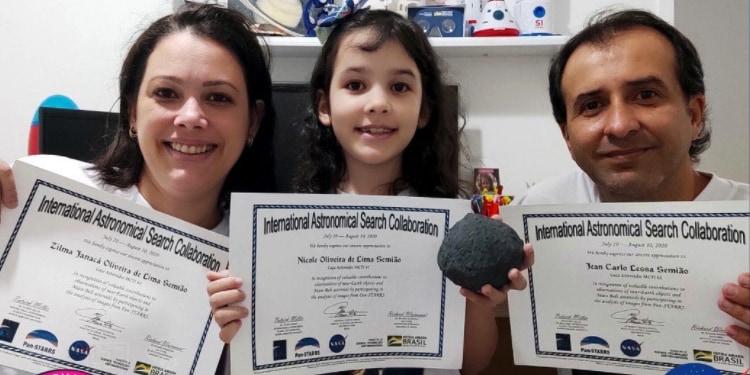 小惑星発見の認定証を手に笑顔のニコルさん(7歳)