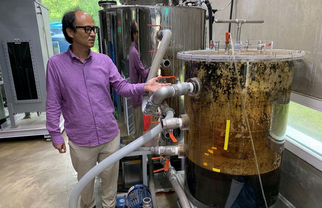 研究所のタンクの横にたつチョ・ジェウェン教授
